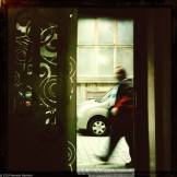 Man walking past doorway, with swirls in the door window